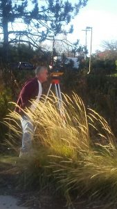Terry surveys in a field using a full transit theodolite.